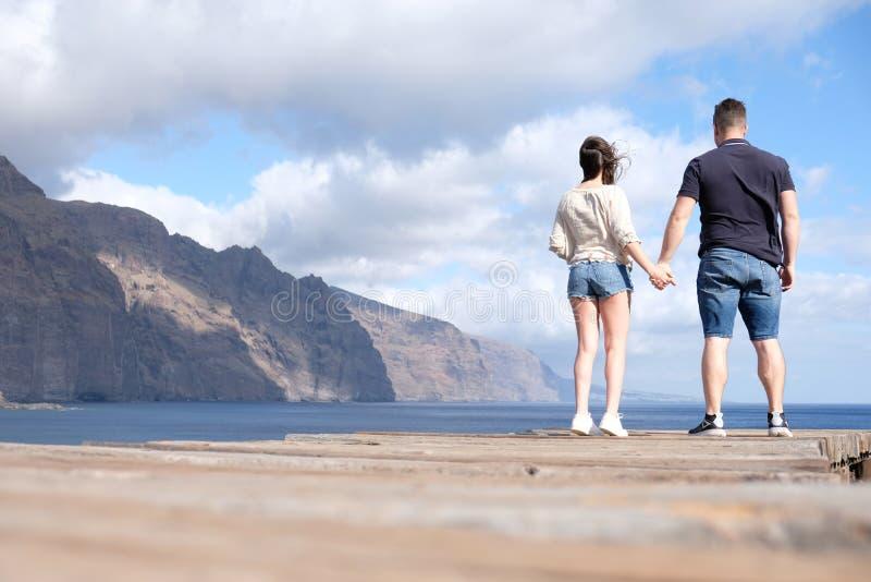 Opinión de ángulo bajo de un par joven que lleva a cabo las manos con los acantilados, el cielo nublado y el mar en el fondo imagenes de archivo