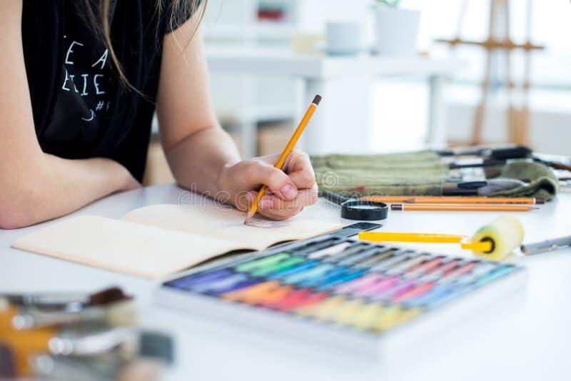 Opinión de ángulo del primer de un proyecto femenino del dibujo del pintor en el sketchbook usando el lápiz Artista que bosqueja  foto de archivo