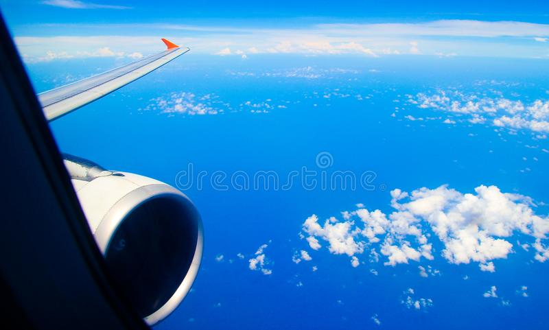 Opinión de ala de aviones sobre las nubes hinchadas y el océano azul imagen de archivo