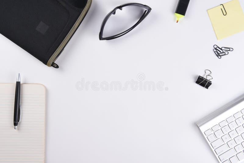 Opinión de alto ángulo de un escritorio blanco del negocio con el cojín, la pluma, el teclado y otros accesorios fotos de archivo