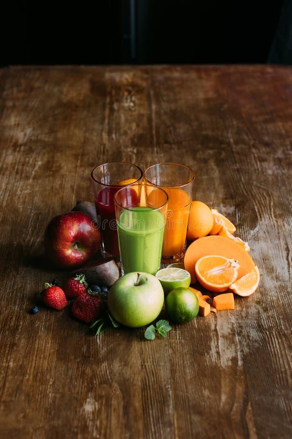 opinión de alto ángulo de diversos smoothies en vidrios y frutas frescas con las verduras en de madera fotografía de archivo libre de regalías