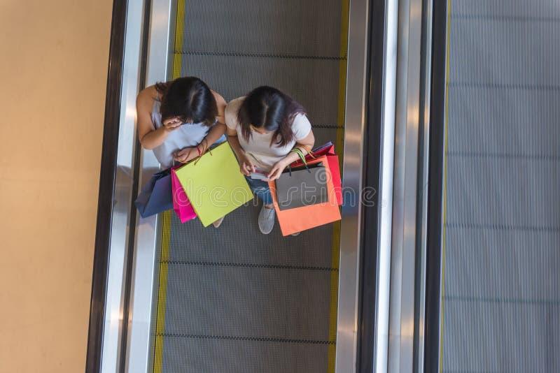 Opinión de alto ángulo dos señoras que sostienen bolsos de compras en la escalera móvil fotos de archivo