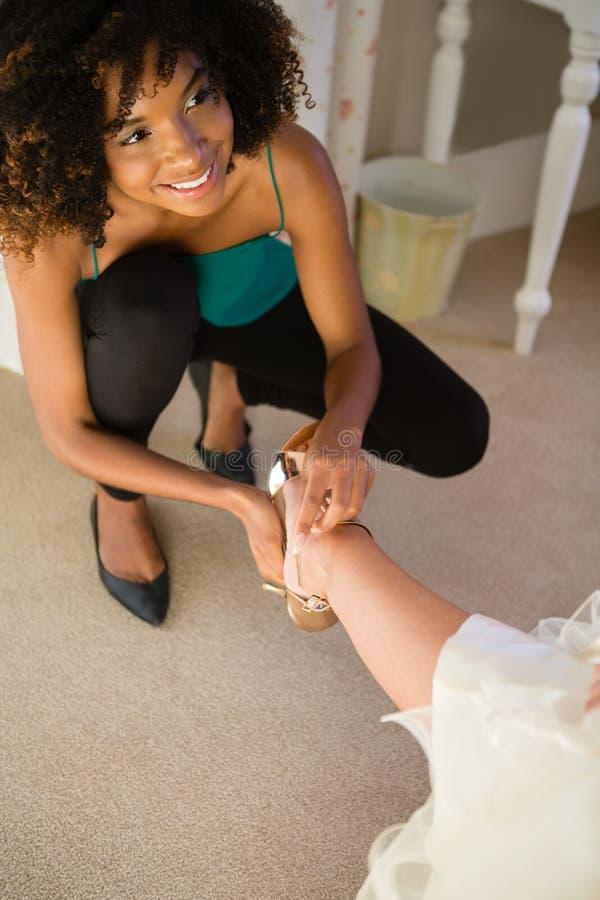 Opinión de alto ángulo el cosmetólogo sonriente que pone en la sandalia a la novia imagenes de archivo
