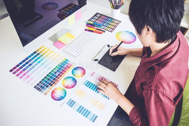 Opinión de alto ángulo el diseñador gráfico de sexo femenino que trabaja en la selección de color y que dibuja en la tableta de g fotos de archivo