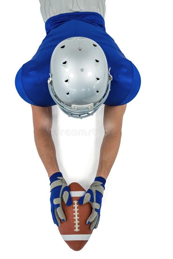 Opinión de alto ángulo el jugador de fútbol americano que alcanza hacia bola fotografía de archivo