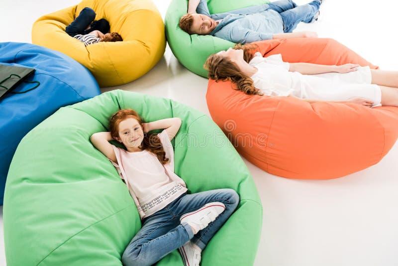 opinión de alto ángulo la familia feliz con dos niños que descansan sobre sillas del puf después de hacer compras foto de archivo libre de regalías