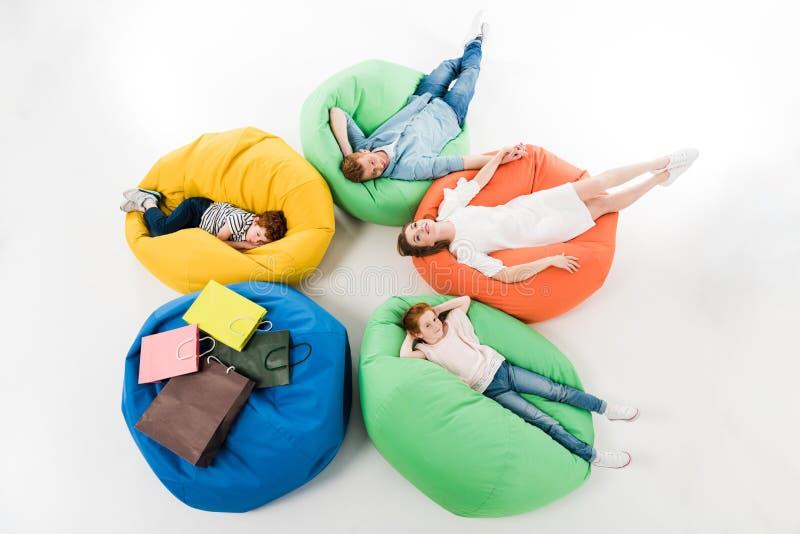 opinión de alto ángulo la familia joven con dos niños que descansan sobre sillas del puf después de hacer compras imagen de archivo