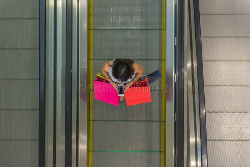 Opinión de alto ángulo la muchacha shopaholic que sostiene el bolso de compras fotos de archivo