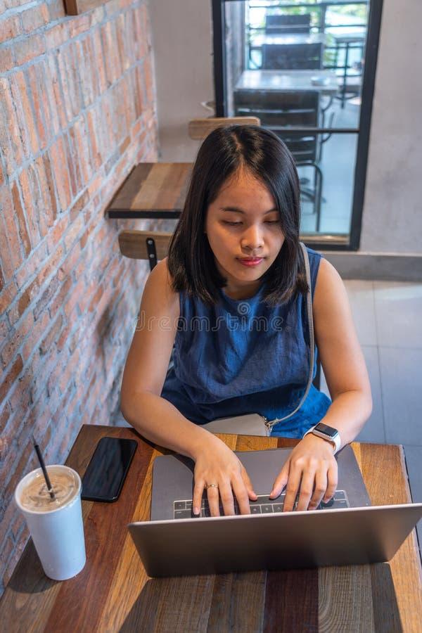 Opinión de alto ángulo la mujer que usa el ordenador portátil en el café rústico fotografía de archivo libre de regalías