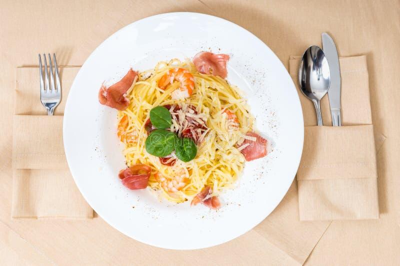 Opinión de alto ángulo de las pastas sabrosas de los espaguetis en la placa blanca en la decoración imagenes de archivo