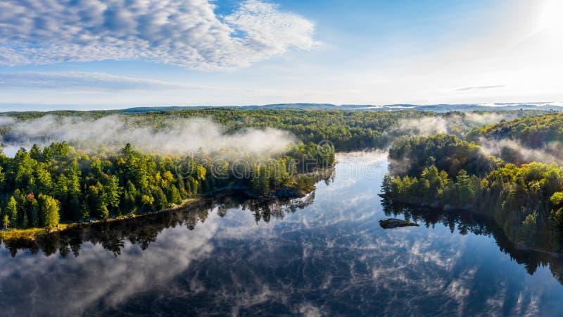 Opini?n de alto ?ngulo de un lago y de un bosque con la niebla imagen de archivo libre de regalías
