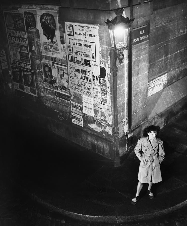 Opinión de alto ángulo una mujer joven que espera al lado de una linterna en una esquina de calle de la oscuridad (todas las pers foto de archivo libre de regalías