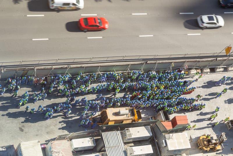 Opinión de Arial un grupo grande de trabajadores de construcción, agrupado en el lado del camino fotos de archivo