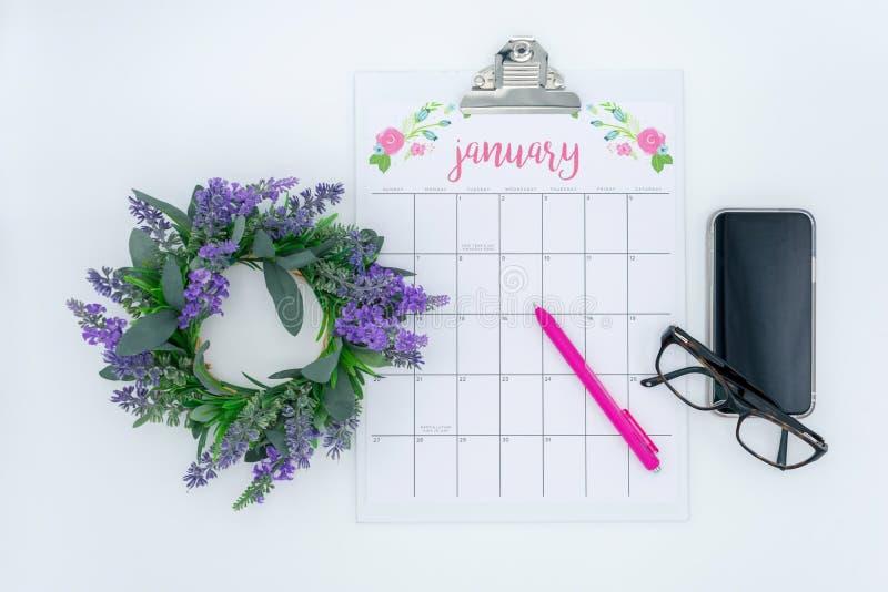 Opinión de arriba del calendario de enero con los vidrios y smartphone imágenes de archivo libres de regalías