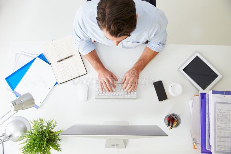 Opinión de arriba el hombre de negocios Working At Computer en oficina imagen de archivo libre de regalías