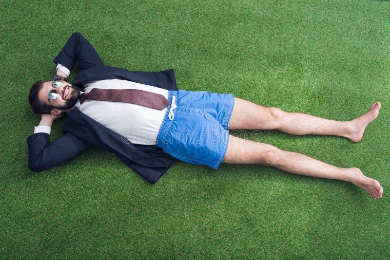 opinión de arriba el hombre de negocios en la reclinación de la chaqueta y de los pantalones cortos fotos de archivo libres de regalías