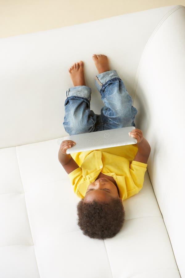 Opinión de arriba el muchacho en Sofa Playing With Digital Tablet fotografía de archivo libre de regalías