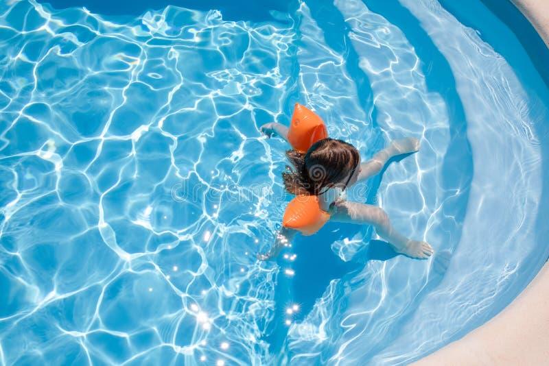 Opinión de arriba el niño relajado con los brazales en las escaleras de la piscina foto de archivo libre de regalías