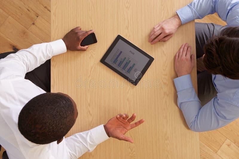 Opinión de arriba empresarios con la tableta de Digitaces en el escritorio foto de archivo