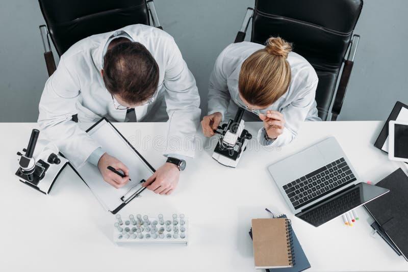 opinión de arriba investigadores científicos en las capas blancas que trabajan junto en el lugar de trabajo foto de archivo