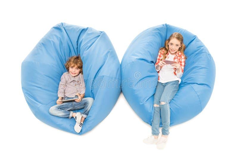 opinión de arriba niños con los dispositivos digitales que descansan sobre sillas del puf imagen de archivo