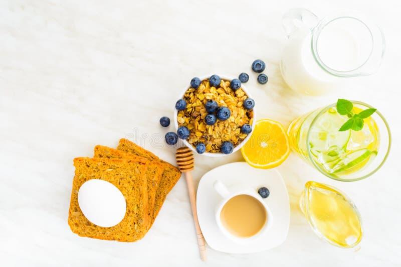 Opinión de arriba sobre la tabla de cena de la mañana con el granola, leche, miel, imágenes de archivo libres de regalías
