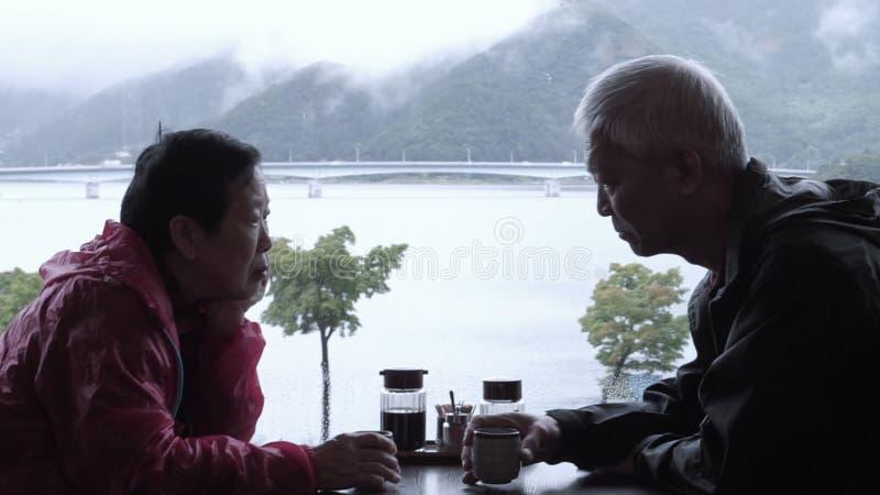 Opinión de consumición de la montaña y del lago del día lluvioso del viaje del té de los pares mayores asiáticos junto imagen de archivo