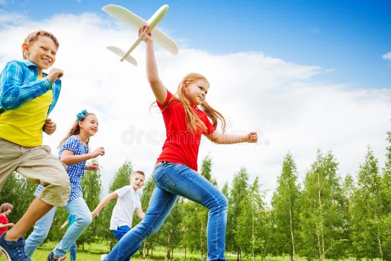 Opinión de debajo de la muchacha que sostiene el juguete grande del aeroplano fotografía de archivo