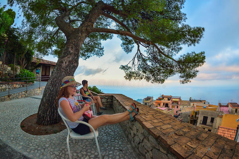 Opinión de goce turística femenina de Taormina en la puesta del sol imagenes de archivo
