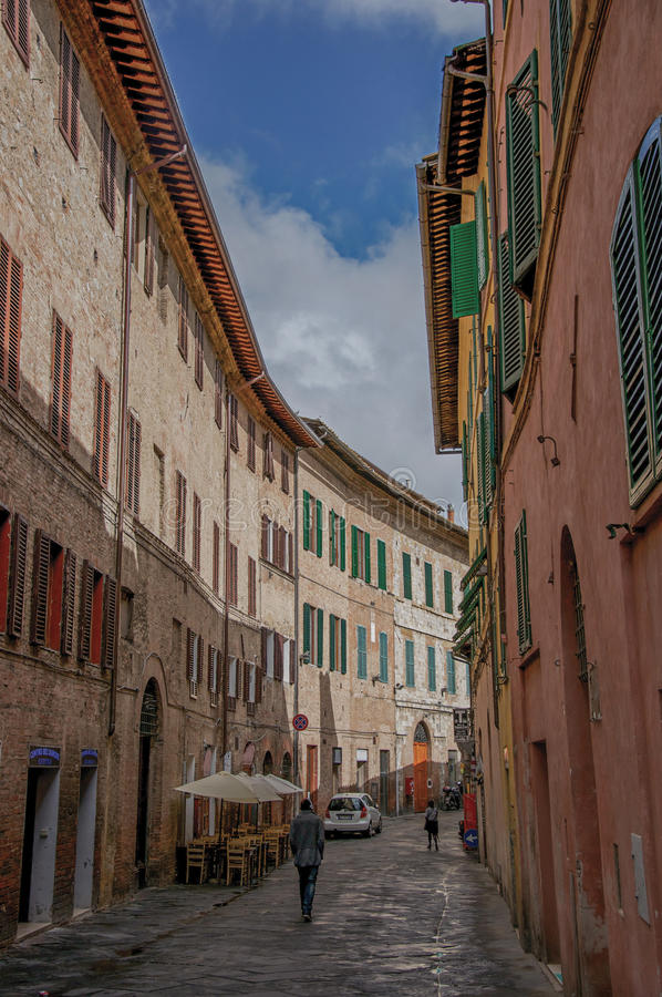 Opinión de la calle y edificios altos en un día nublado en Siena imágenes de archivo libres de regalías