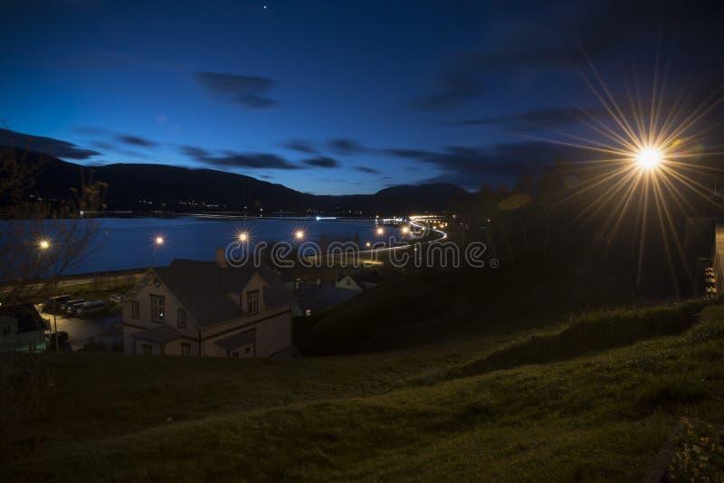 Opinión de la ciudad con el lightlail del coche en el camino la noche del invierno, Akureyri, fotos de archivo libres de regalías