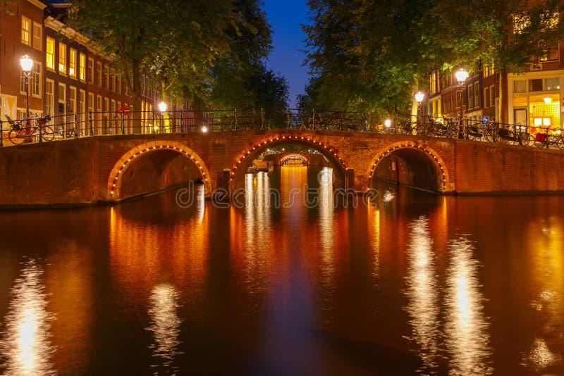 Opinión de la ciudad de la noche de los canales de Amsterdam y de siete puentes fotos de archivo