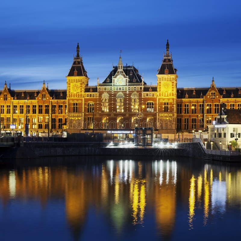 Opinión de la ciudad de la noche del canal de Amsterdam y de la estación de Centraal imágenes de archivo libres de regalías