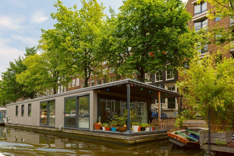 Opinión de la ciudad del canal y de la casa flotante, Holanda, Países Bajos de Amsterdam foto de archivo libre de regalías