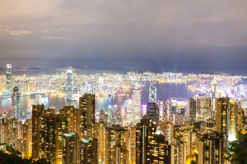 Opinión de la ciudad de Hong Kong del pico de Victoria en la noche con una sinfonía de la demostración ligera fotos de archivo libres de regalías