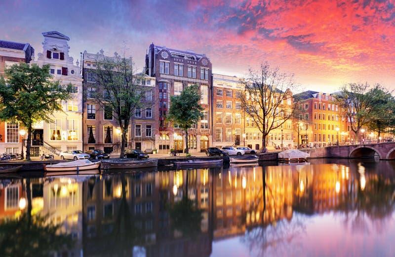 Opinión de la ciudad de la puesta del sol de Amsterdam, los Países Bajos con el río de Amstel imagenes de archivo