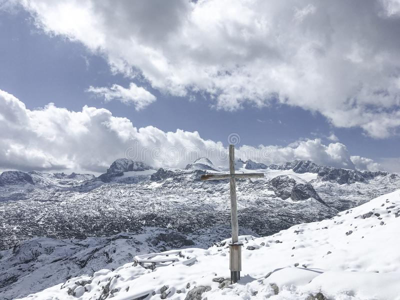 Opinión de la cordillera de Dachstein con una cruz fotografía de archivo libre de regalías