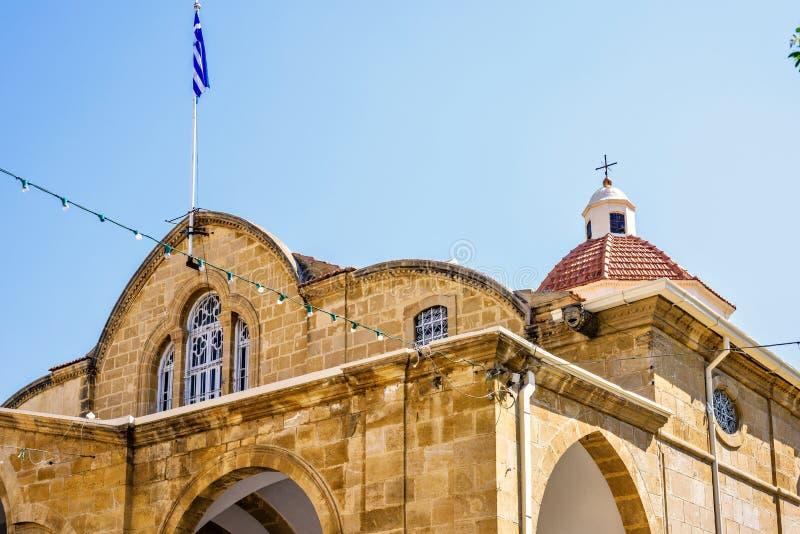 Opinión de la luz del día al tejado de la iglesia de Faneromeni con la bandera griega fotografía de archivo