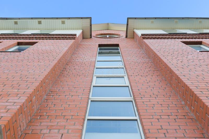 Opinión de la luz del día de la parte inferior a la fachada del ladrillo rojo del edificio moderno Cielo azul brillante en fondo imagenes de archivo