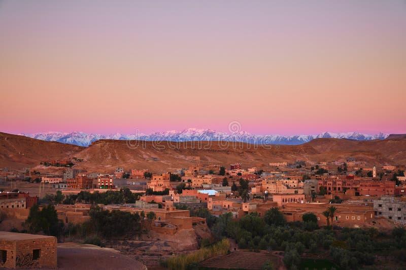 Opinión de la mañana de la ciudad del desierto de Ait Ben Haddou y de las montañas de atlas nevadas en el fondo fotografía de archivo libre de regalías