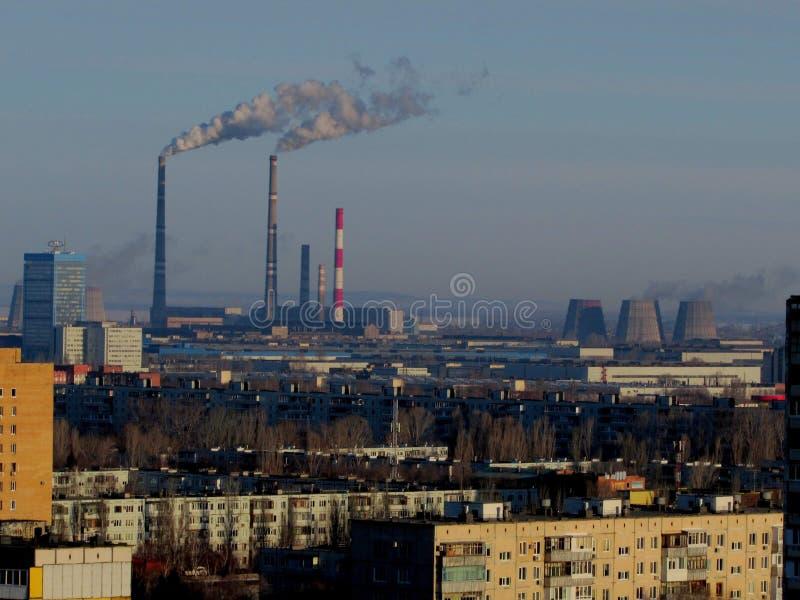 Opinión de la mañana de las construcciones de viviendas residenciales y de los tubos que fuman del calor y central eléctrica en l fotografía de archivo