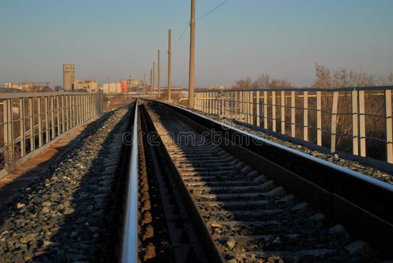 Opinión de la mañana de la pista ferroviaria en el fondo de edificios industriales y del cielo azul imagen de archivo