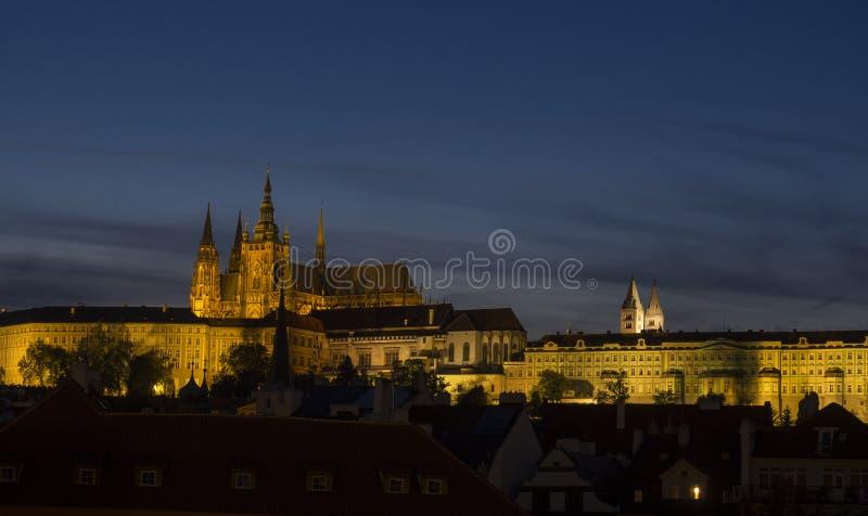 Opinión de la noche del churche del St Vitus Cathedral y del panorama góticos iluminados del castillo de Praga con el cielo hradc fotos de archivo
