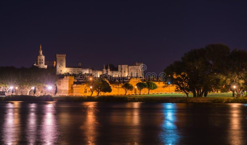 Opinión de la noche del puente del St Benezet con el palacio del papa en Aviñón, Francia el río Rhone en primero plano fotografía de archivo