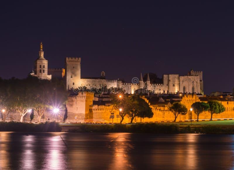 Opinión de la noche del puente del St Benezet con el palacio del papa en Aviñón, Francia el río Rhone en primero plano foto de archivo