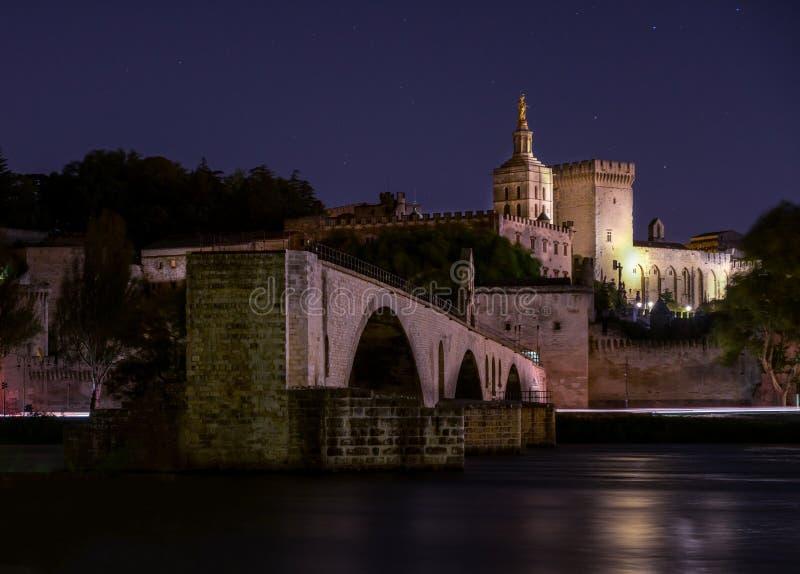 Opinión de la noche del puente del St Benezet con el palacio del papa en Aviñón, Francia el río Rhone en primero plano foto de archivo libre de regalías