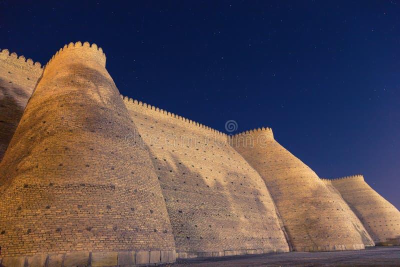 Opinión de la noche de los fortess históricos de la arca en la ciudad de Bukhara, Uzbekistán Pared de la fortaleza de Bukhara, la imagen de archivo libre de regalías