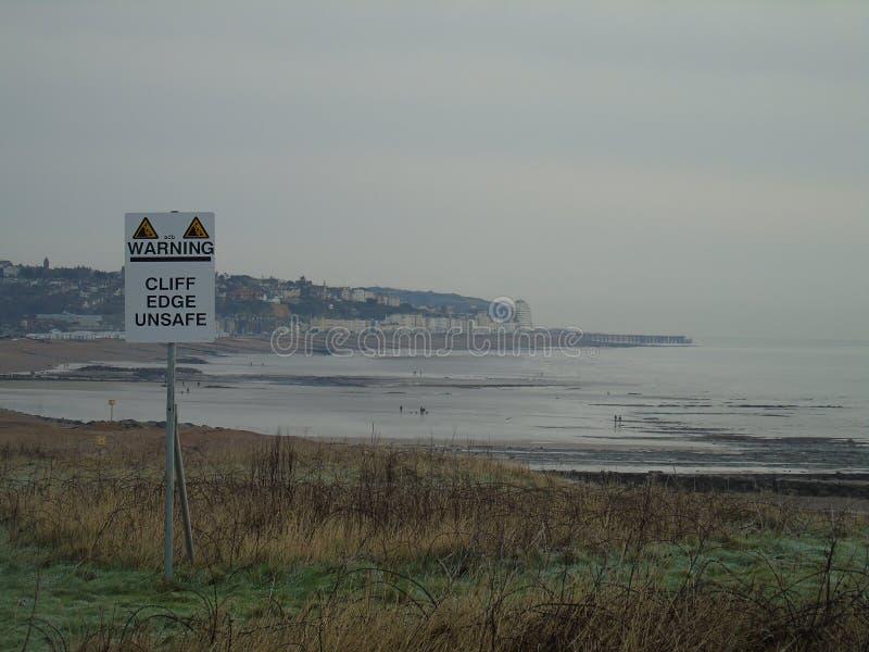 Opinión de la orilla del mar de Hastings con la señal de peligro imagen de archivo libre de regalías