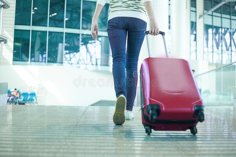 Opinión de la pierna una mujer en prisa con el bolso del tamaño de la cabina en aeropuerto foto de archivo libre de regalías