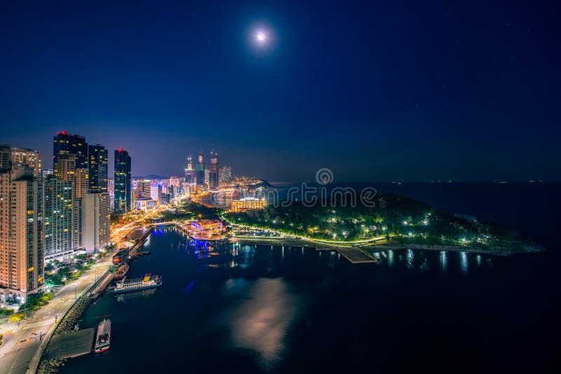 Opinión de la playa de Busán del top del tejado del hotel en la ciudad de Busán en noche con el cielo azul y la Luna Llena foto de archivo libre de regalías